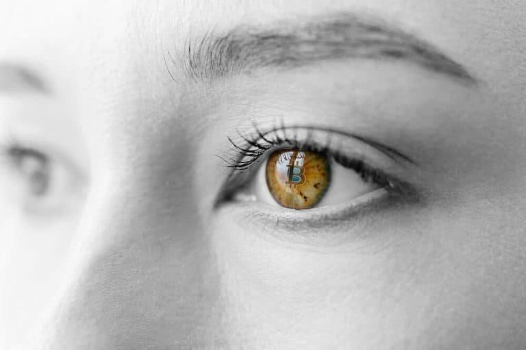 Person's eye with Bitcoin (BTC) on their eye
