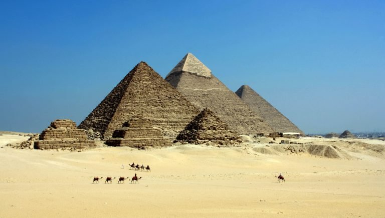 Pyramids in the desert with blue skies on a sunny day.