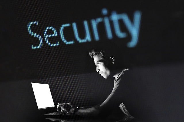 Man on laptop with 'Security' printed above his head