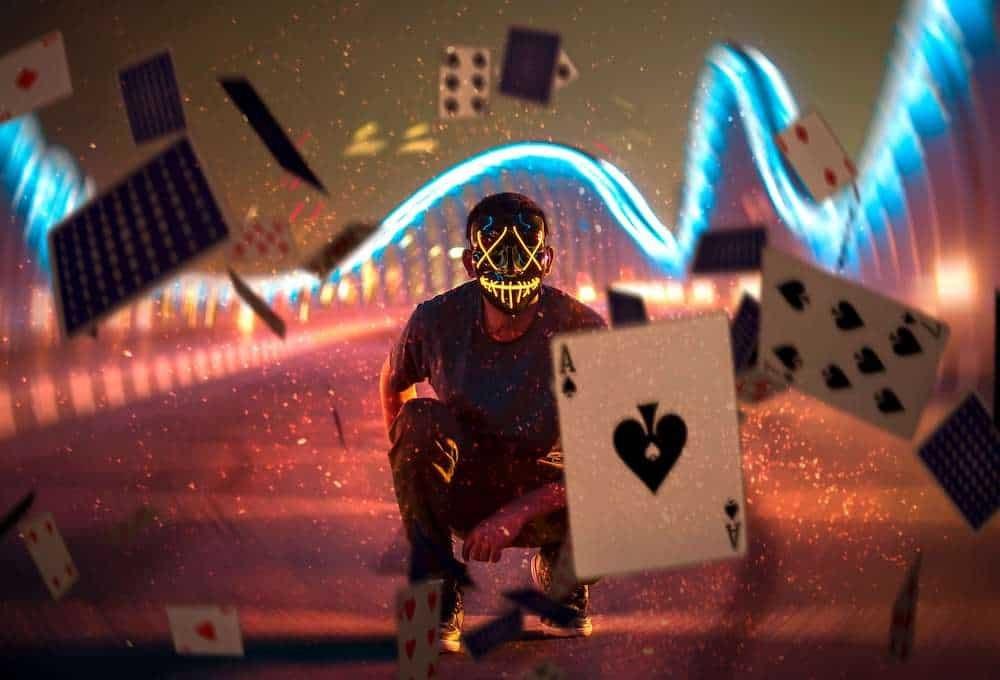 Electronic joker-themed masked man throwing cards
